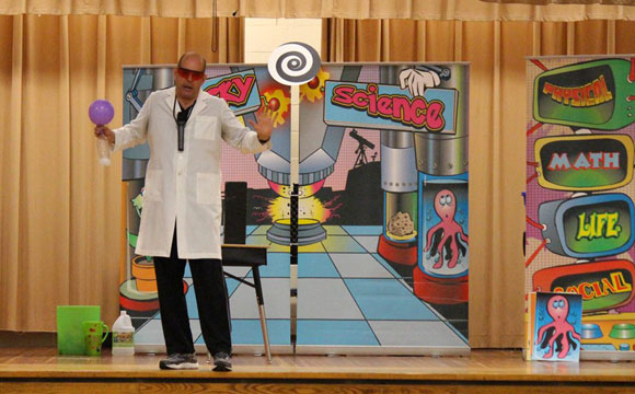 Doug Scheer onstage performing comedy and science show for schools